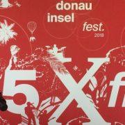 """Rotes Banner zum DIF18 mit Schrift in weiß """"35 mal frei"""" hinter einem Tisch mit 2 Mikrophonen"""
